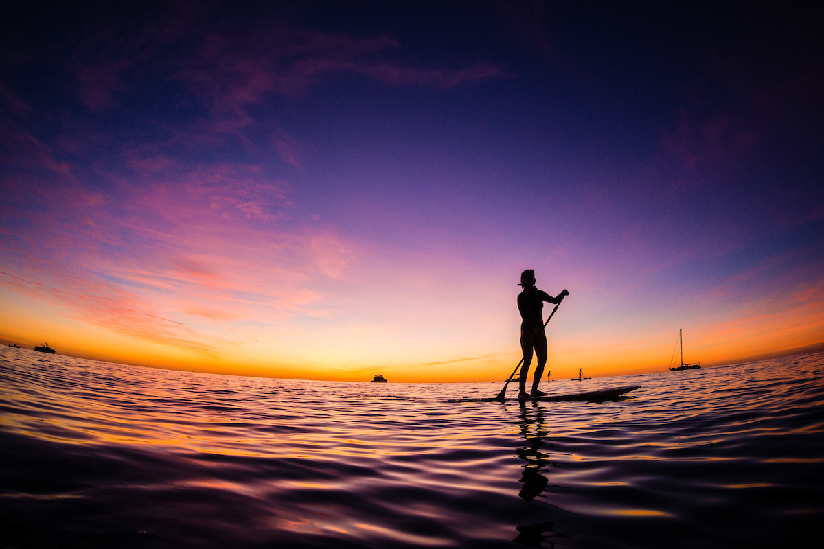 Woman Stand Up Paddle Boarding at dusk, Lady Elliot Island, Great Barrier Reef, Queensland, Australia